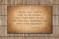 Patton quote. Never tell people how to do things. Tell them what to do and they will surprise you with their ingenuity.- George S. Patton. Quote over stone and Royalty Free Stock Images