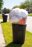 Pattumiera del bidone della spazzatura in pieno di immondizia sul prato inglese della via Fotografia Stock
