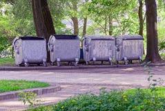 Pattumiere grige dalla strada vicino agli alberi nel parco fotografia stock libera da diritti