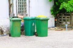 Pattumiere verdi del recipiente dei rifiuti di cestino esterne e bordo della strada confuso del fondo della parete nella città co Fotografia Stock Libera da Diritti