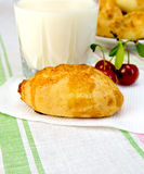 Patty with cherries and milk on tablecloth. Pie with cherries on a paper napkin, a glass of milk on a linen tablecloth background Royalty Free Stock Photography