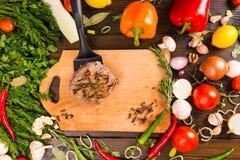 Patty en la espátula y los veggies sobre tabla de cortar Imagen de archivo
