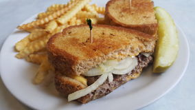 Patty melt with french fries and a dill pickle. Patty melt on rye bread with sauteed onions, crinkle cut french fries, and a dill pickle spear royalty free stock photo
