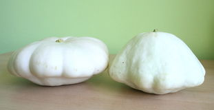 Pattypan squash. Two pattypan squashes on a brown desk stock photo