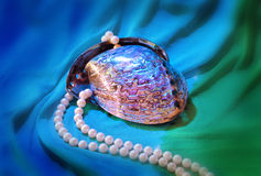 Paua-Oberteil und Perlenhalskette auf blaugrünem Drapierung Stockfotografie