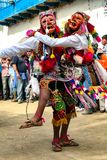 Men dancing and wearing typical masks at Paucartambo's religious festival of Virgen del Carmen. stock photo