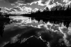 Lake and forest with dramatic clouds reflected in black and whit. Black and white image of dramatic clouds reflected in Paudash Lake Ontario with dark stock photos