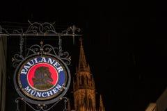 Paulaner在慕尼黑新市镇霍尔Neues Rathaus前面的啤酒商标在晚上 免版税库存图片