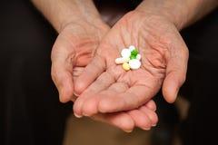 Paume avec des pilules et des vitamines Images stock