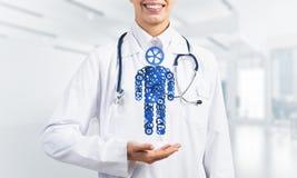 Paume de docteur de femme montrant le chiffre fait en mécanisme de vitesse comme symbole pour l'organisation d'individu Photographie stock
