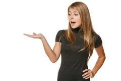 Femme étonnée montrant l'espace de copie sur la paume Image stock