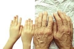 Paumes pour les enfants et le vieil homme sur le papier chiffonné, un symbole de l'avenir et le passé Photos libres de droits