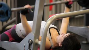 Paurlifting. The sports woman. Gym. The woman lifts heavy weight lying on a back. Training. The man does exercises