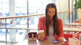 Pausa caffè - una donna attraente di affari che beve un caffè per andare fare una chiamata sul suo smartphone stock footage