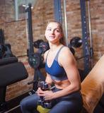 Pausa de formação, jovem mulher desportiva no sportswear que descansa no banco que guarda pesos em suas mãos no gym fotos de stock