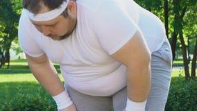 Pausa que hace masculina gorda a respirar y que corre adelante, meta de la pérdida de peso metrajes