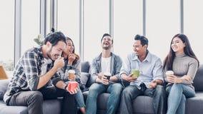 Pause-café créative de prise de concepteur au cafétéria de bureau employé de multiethnics s'asseyant au sofa et parlant et a photo stock