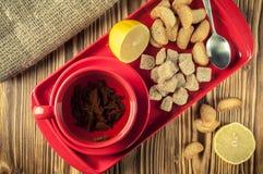 Pause café thé dans un plat en céramique rouge sur un plateau avec du sucre, les biscuits et le citron de canne sur un fond en bo images libres de droits