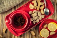 Pause café thé dans un plat en céramique rouge sur un plateau avec du sucre, les biscuits et le citron de canne sur un fond en bo photos stock
