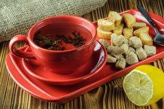 Pause café thé dans un plat en céramique rouge sur un plateau avec du sucre, les biscuits et le citron de canne sur un fond en bo photo stock