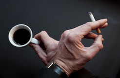 Pause with coffee and cigarette. Hand idolated on black at pause with coffee and cigarette Royalty Free Stock Images