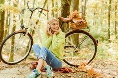 Pause musicale Enjoy détendre la bicyclette de tour de fille de forêt pour l'amusement Automne chaud Fille avec la bicyclette et  image stock