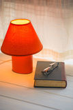 Pause on reading. Red desk lamp, book and glasses on window sill. copy space Stock Image