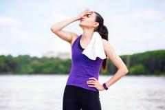 Pause und Erholung vor oder nach Training und Betrieb im Park Attraktive Frau auf purpurrotem T-Shirt, auf Naturhintergrund lizenzfreies stockbild
