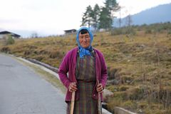 Pause variopinte della donna da lei lavoro nel Bhutan rurale Immagine Stock