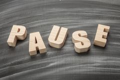 Pause. Wooden letters Pause on blackboard Stock Image