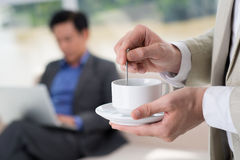 Pause at work. Close-up of human hands preparing tea on the foreground Royalty Free Stock Images