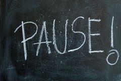 Pause written in chalk on a blackboard Stock Photo