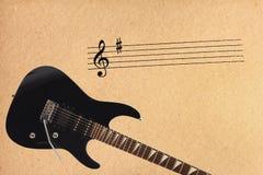 Pauta musical das notas e guitarra elétrica preta da rocha na parte inferior do fundo áspero do cartão Fotos de Stock