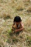 Pauvre enfant sur le pré d'herbe sèche Photo stock