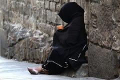Pauvre femme priant se reposer dans la rue images stock