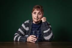 Pauvre femme supérieure avec le verre de l'eau se reposant à la table photos libres de droits