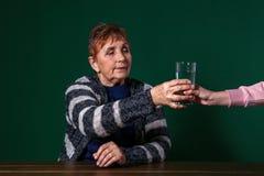 Pauvre femme supérieure prenant le verre de l'eau sur le fond de couleur photos libres de droits