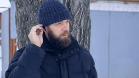Pauvre homme barbu en hiver écoutant la musique sur des écouteurs par l'intermédiaire du téléphone clips vidéos