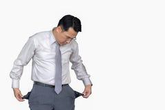Pauvre homme d'affaires asiatique se tenant montrant les poches de pantalon vides d'isolement sur le fond blanc, concept de la fa photos stock