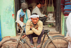 Pauvre homme heureux s'asseyant avec son cycle sur la rue Photo stock