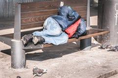 Pauvre homme ou réfugié sans abri dormant sur le banc en bois sur la rue urbaine dans la ville, concept documentaire social Photo stock