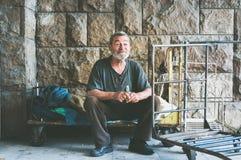 Pauvre homme sans abri heureux et souriant s'asseyant dans l'ombre du bâtiment sur la rue urbaine dans la ville Photo stock