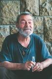 Pauvre homme sans abri heureux et souriant s'asseyant dans l'ombre du bâtiment sur la rue urbaine dans la ville Photographie stock libre de droits