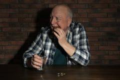 Pauvre homme sup?rieur avec du pain et le verre de l'eau ? la table image stock