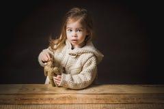 Pauvre petite fille jouant avec un ours de paille Image libre de droits