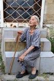 Pauvre vieille femme bulgare avec la canne de marche et portée, robe minable se reposant sur des escaliers sur la rue de Varna Photos stock