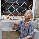 Pauvre vieille femme bulgare avec la canne de marche et portée, robe minable se reposant sur des escaliers sur la rue de Varna Images stock