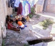 Pauvres enfants jouant au sol à côté d'une décharge Images libres de droits