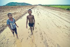 Pauvres gosses cambodgiens jouant dans la boue Photo stock