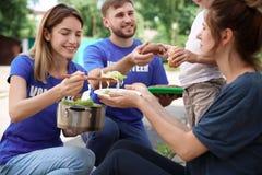 Pauvres personnes recevant la nourriture des volontaires image libre de droits